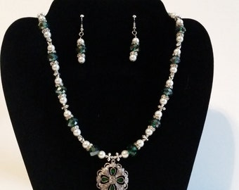 Green and Silver toned cross necklace with matching earrings.