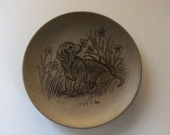 13cm Poole pottery plate puppy sniffing flowers design by Barbara Linley Adams Good condition. 13 cm stoneware.