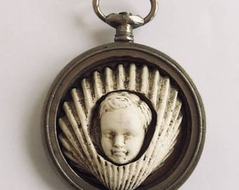Shell and child in a silver watch