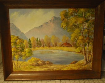Vintage Oil landscape painting of lake with cabin surrounded by trees and mountains.