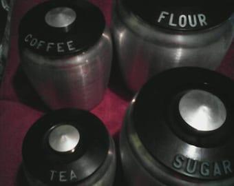 4 Piece Aluminum Canister Set. Black lids with aluminum knobs. Coffee,Tea,Flour and Sugar. Excellent condition.