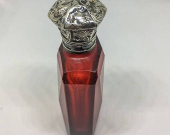 Victorian perfume bottle in ruby red glass with silver repousse cap