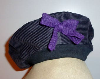 woman in dark grey velvet and purple bow beret