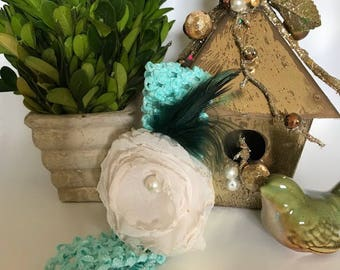 Beautiful teal and ivory colored headband with the touch of a few feathers and center pearl