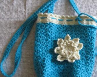 Blue shoulder bag and its large off-white flower