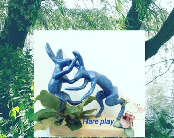 Hare  play . Clay & Wire Sculpture on a Wooden base . With small silk flowers and leaves adorning the blue Hares as they Box...