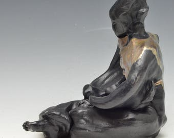 Black and Gold Figure Seated in Meditation in Raku Ceramics