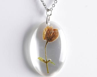 Oval-shaped resin pendant with Clematis's flower