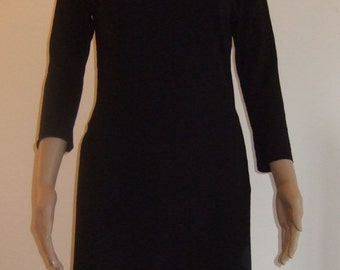 The black dress in two parts, consisting of a tunic and a skirt made from the same fabric