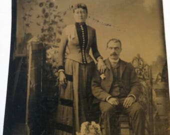 Vintage Tintype Photo of Woman Standing and Man sitting. They are dressed in Dress Clothes.