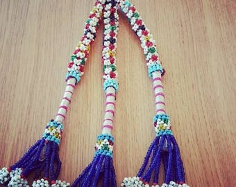 Borlon Kuchi of beads of different colors and piece of metal.
