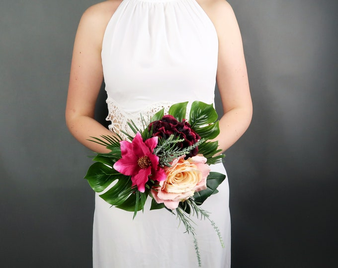 Small bridesmaids bouquet with tropical flowers in fuchsia, burgundy and peach