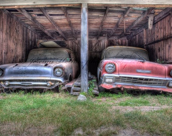 Pair of 50s chevrolets sit covered in dust and rust in an old barn fine art print