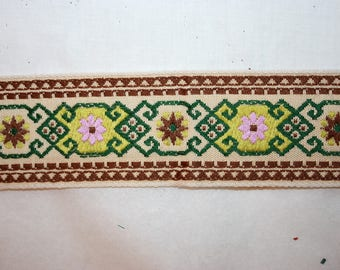 "Over 5 FEET of 1 7/8"" wide woven trim in greens brown and pink on a beige background"