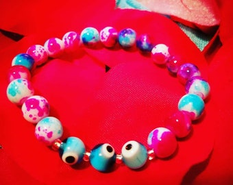 "Three evil eye beaded bracelet. Blue, pink and white beads. Blue evil eye. Model's wrist is a 6.5""."