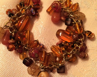 Vintage Glass Bead Cha Cha Style Bracelet in Golds, Browns. There Are All Kinds and Shapes of Fun Beads. It is About 7 1/2 Inches Long (D22)