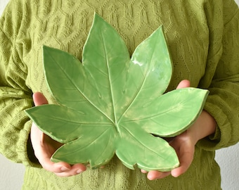 Een keramieke schaal in de vorm van een lente blad | Groene bladeren als schaal afgebakken en geglazuurd