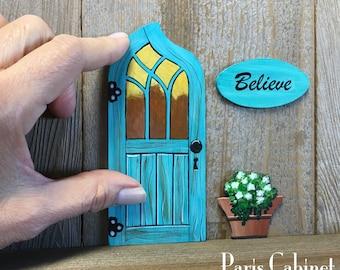 Fairy door set, teal door with window, Believe sign and flower pot mount with museum putty, included