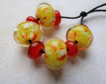 lampwork yellow and red encased glass bead set, uk handmade