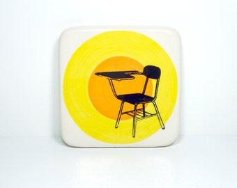 art tile/trivet of a school desk, perhaps in detention, on a color block of yellow and orange, made to order.