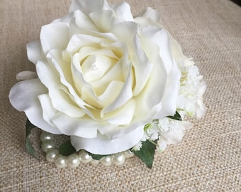 Ivory and cream silk wedding wrist corsage. Made from an artificial rose, gypsophila, ranunculus, hydrangea and greenery.