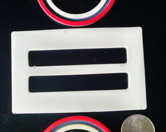 three vintage buckles, two red white blue one large white