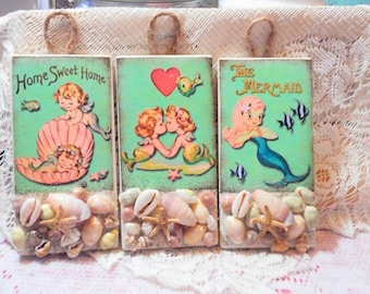 Darling trio set of vintage baby mermaids on hanging tiles.