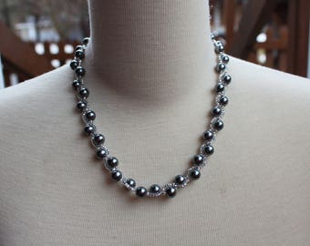 Grey necklace woven with glass beads