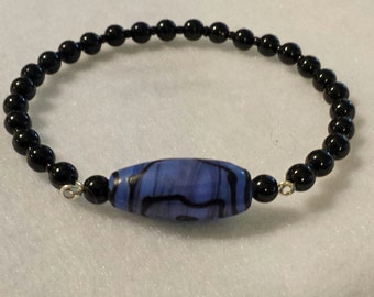 Bracelet. Black memory wire bangle with denim blue and black painted glass focal bead. Free shipping!