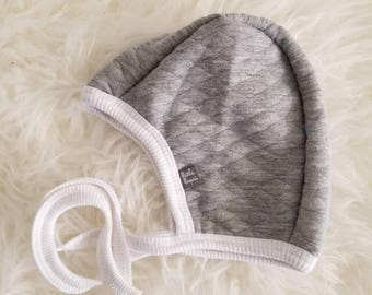 Quilted Grey pilot hat by Little Lapsi. Heathered Pink Baby hat with ties.