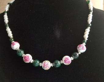 Delicate rose accented glass beads surrounded by classic pearl design