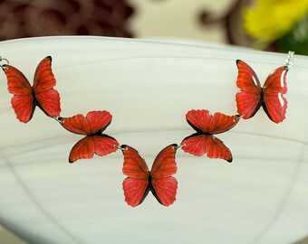 Red five butterflies necklace. They look real, but are man-made and vegan. Comes in lovely jewellery box.