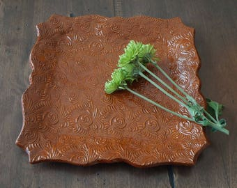 Handmade, decorative plate, detailed pattern, burnt orange