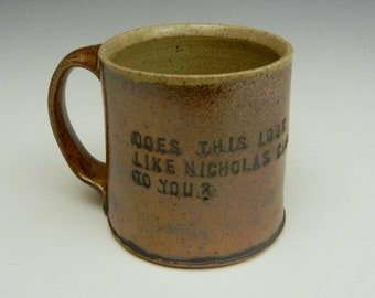 Salt/Soda fired stoneware mug with stamped text and a snake
