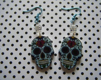 Light blue detailed sugar skull earrings with iridescent glass beads on metallic blue ear wires