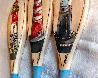 A set of three woodburned and painted lighthouse spoons