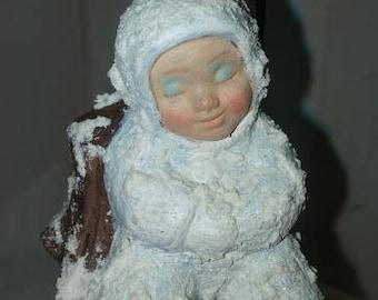 Snow Baby Ornament Beside Stump
