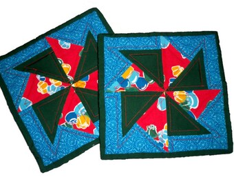 Two Quilted Pot Holders or Hot Pads in blue, red, and green bold print fabrics