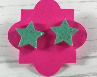 Star shaped resin earrings with embedded glitter, pierced.