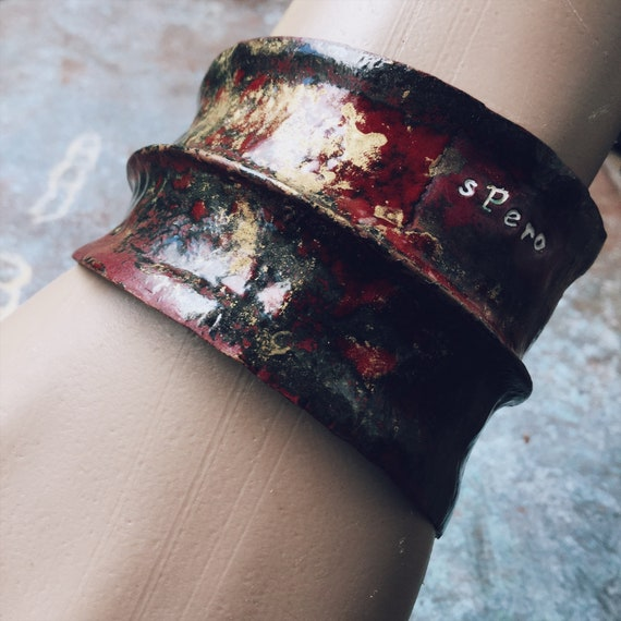 'Spero' (I Hope'): distressed red and gold fold formed anticlastic asymmetric cuff, copper enamel