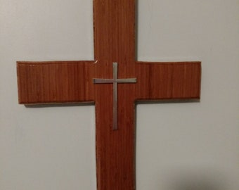 Cross handcrafted out of bamboo wood with decorative silevr cross mounted in center with clear gloss laquer.