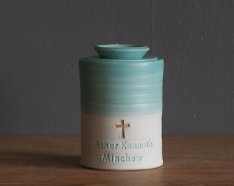 child size urn with lid. urn for human ashes, infant urn. shown in satin turquoise on porcelain clay with gold cross