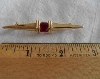 Vintage costume jewelry pin with ruby colored gemstone