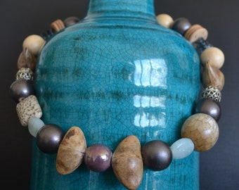 Soft lilac ceramic beads, triangular seeds, laminated wood, metal, fossil coral, coconut, Czech glass and a chapter lock.
