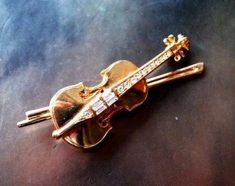 Callsy vintage 80s,bold, gold tone metal ,figural,violin brooch with clear crystals. Made by Swarovsky.