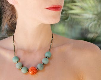 Short one-piece necklace made of coral carved, jade and hematite beads.