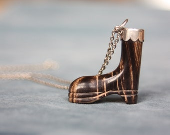 A carved horn boot, with a silver fixing and chain.