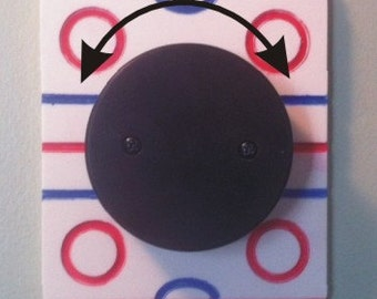 Hockey light switch cover with rotating puck