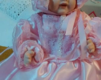 A porcelain doll dressed in pink. Hat,dress, petticoat, ribbons and lace.