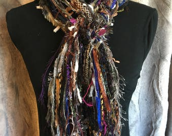 Unique fashion scarf in shades of purple, brown, blue, black, green and grey.
